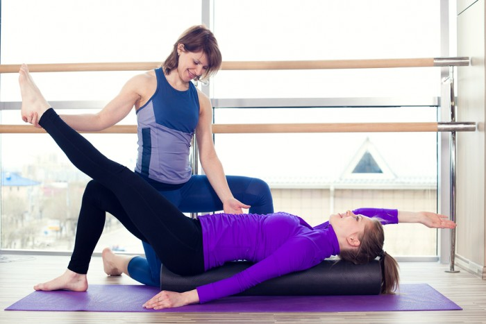 Aerobics Pilates personal trainer helping women group in a gym class